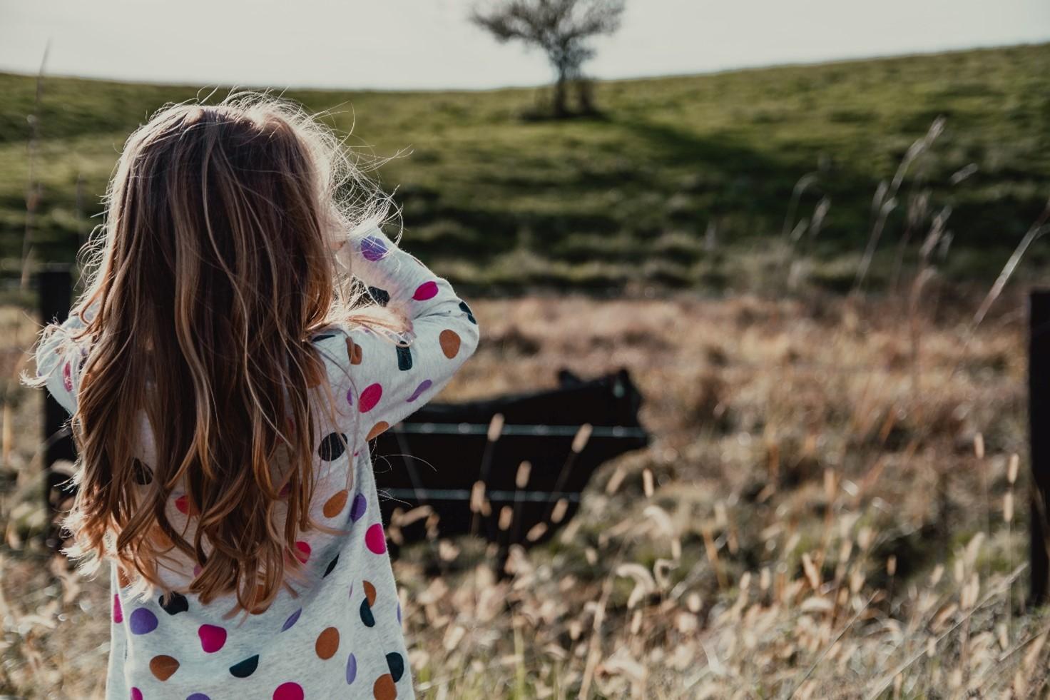 Pieni tyttö katselee ylös kukkulalle ulkona puistossa